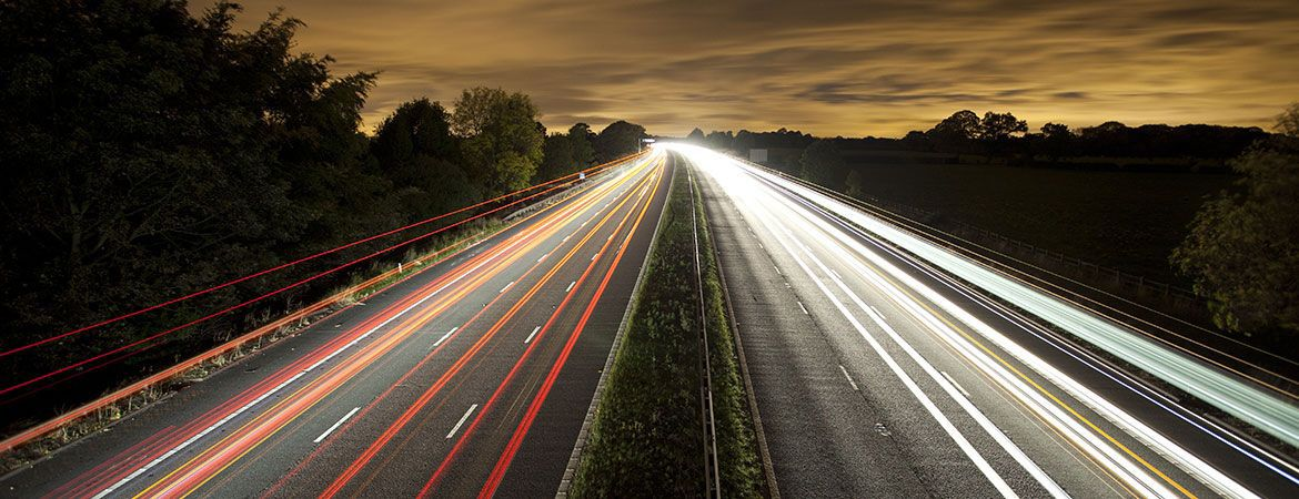 Home: Fast red and white streams of traffic at night on the motorway.